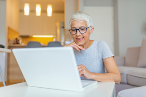 Senior woman sitting at table, smiling at her computer screen.