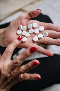 Woman's hands with red nail polish, sorting through round white pills on her open palm.
