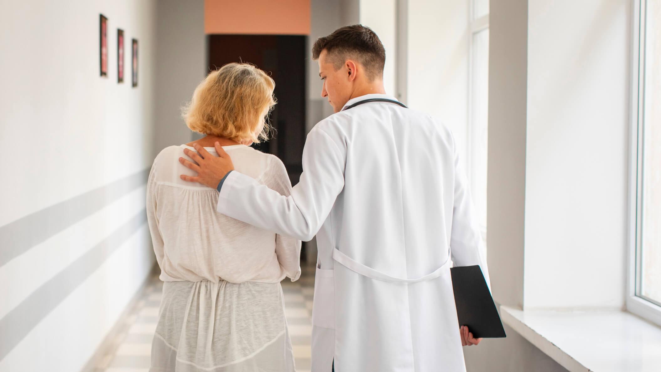 Bilde av en lege ved siden av en pasient.