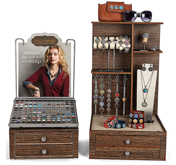 a wooden stand that says create your own style in a snap and has a woman looking at the user. Many bracelets and necklaces hanging from it.