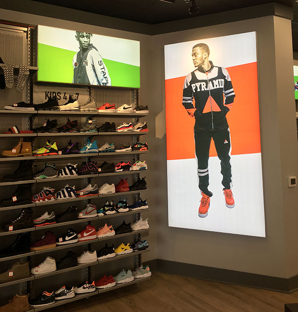 shelves full of shoes next to a wall banner of a man in a sweater.