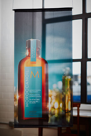 a large standing display banner with a moroccan oil bottle featured prominanly