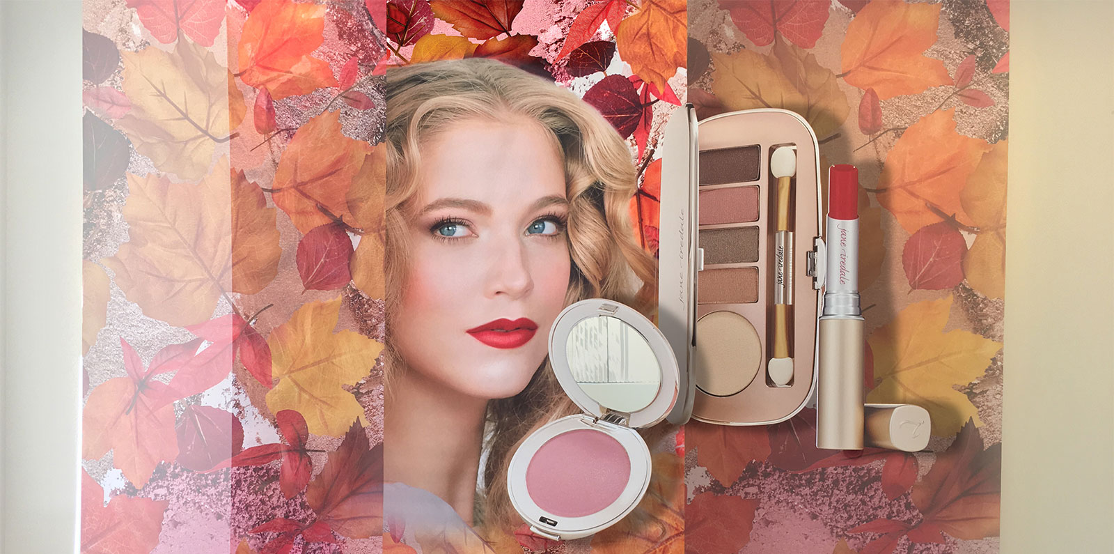 a womans face surrounded by pink leaves and various cosmetics