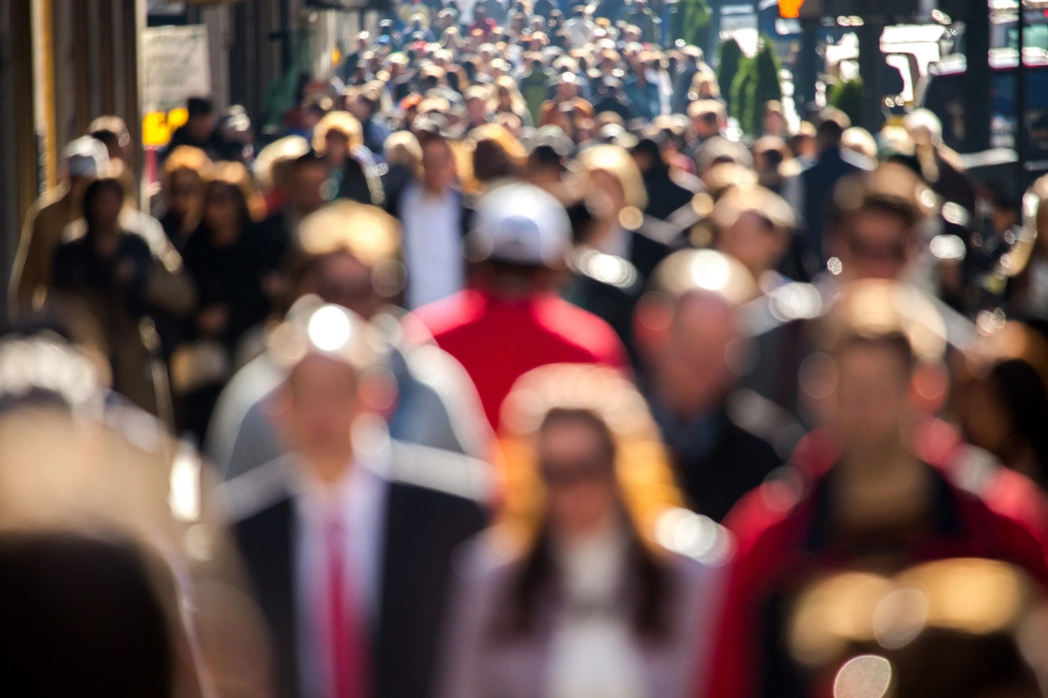 a large croup of people crowded on a street, blurred