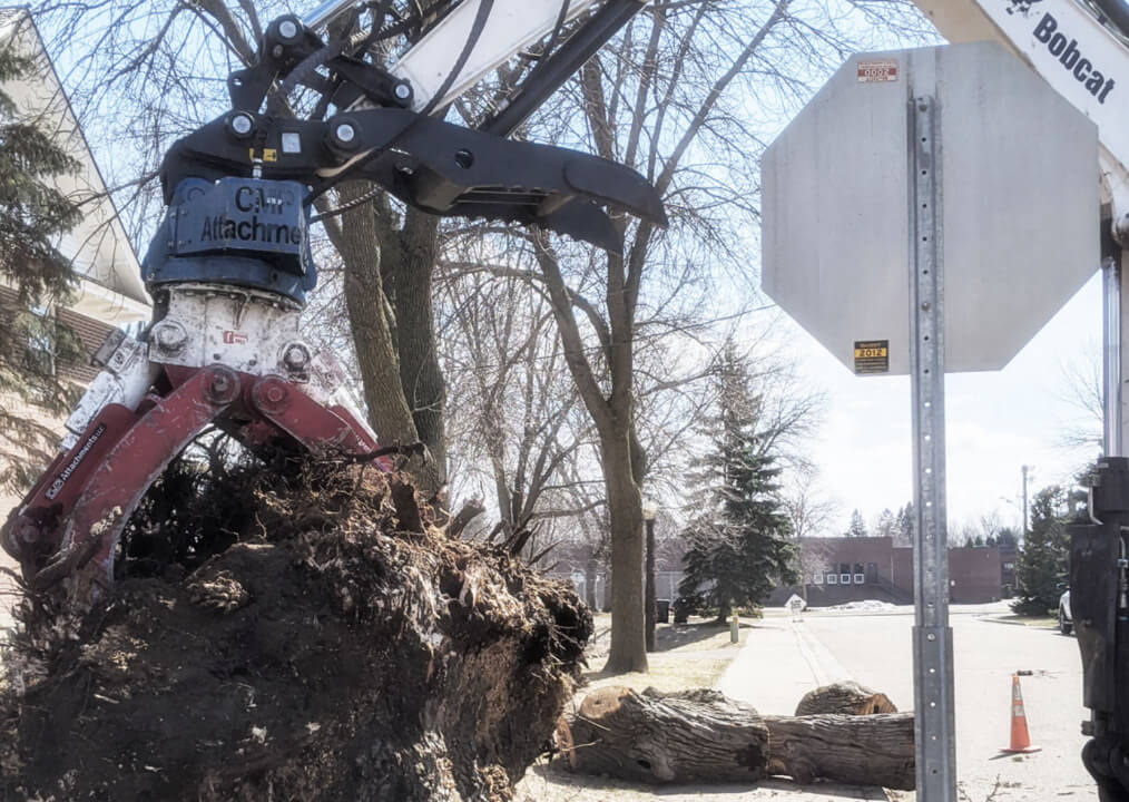 Arm of Bobcat excavator pulling stump from the ground in front of a home. TreeStory handles select residential tree services