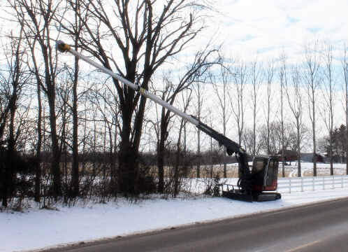 The Loftness Kwik Trim, commercial tree trimming machinery, trimming trees in the winter by a highway for ROW maintenance