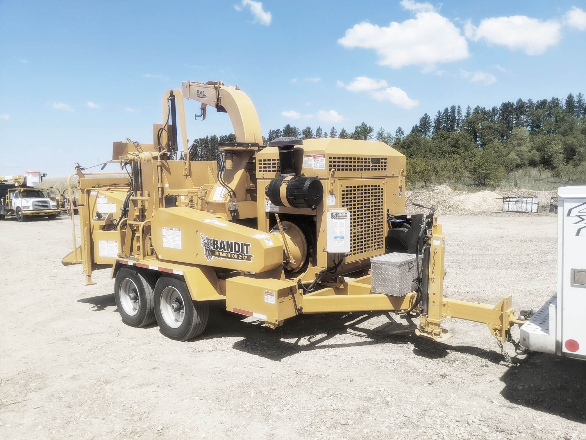 Yellow Bandit 21 XP Wood Chipper parked on gravel lot. Commercial tree equipment that allows for quick, easy removal of trees