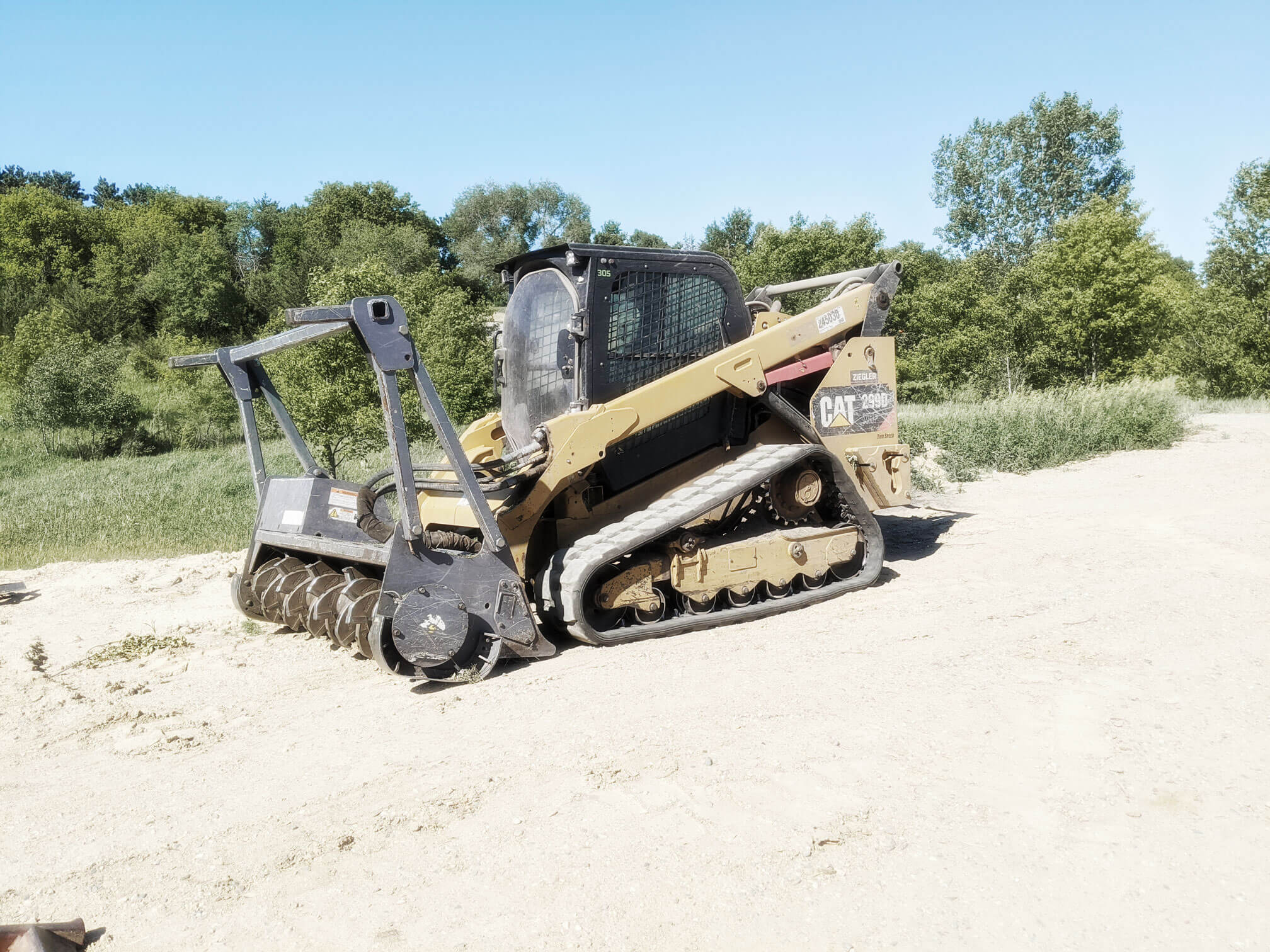 CAT skidsteer with Loftness Mulching Head parked on gravel with vegetation behind. Great for clearing unwanted vegetation