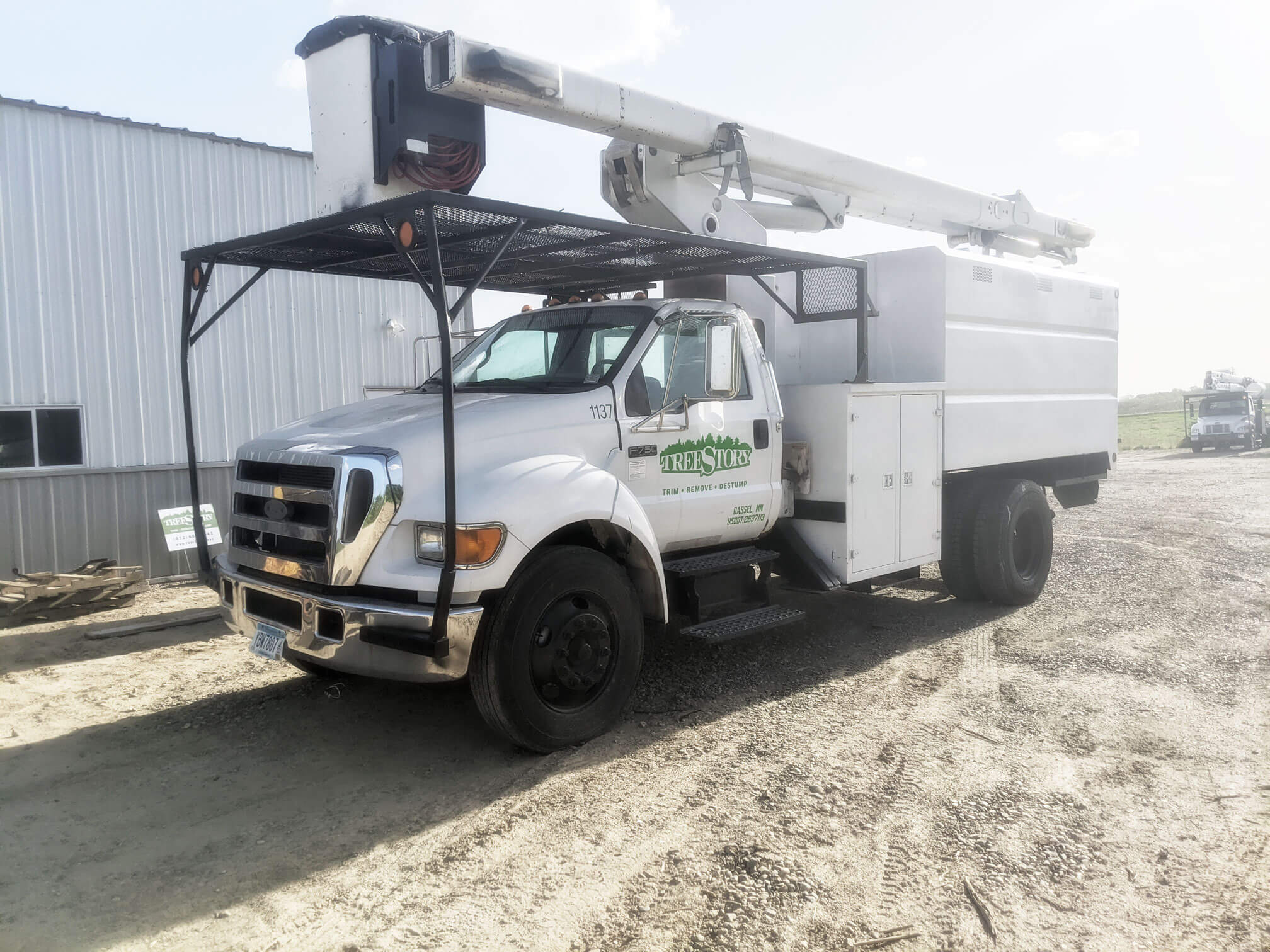 Treemaster truck parked on gravel behind metal shed. This allows TreeStory to cut in tight spaces for commercial tree projects