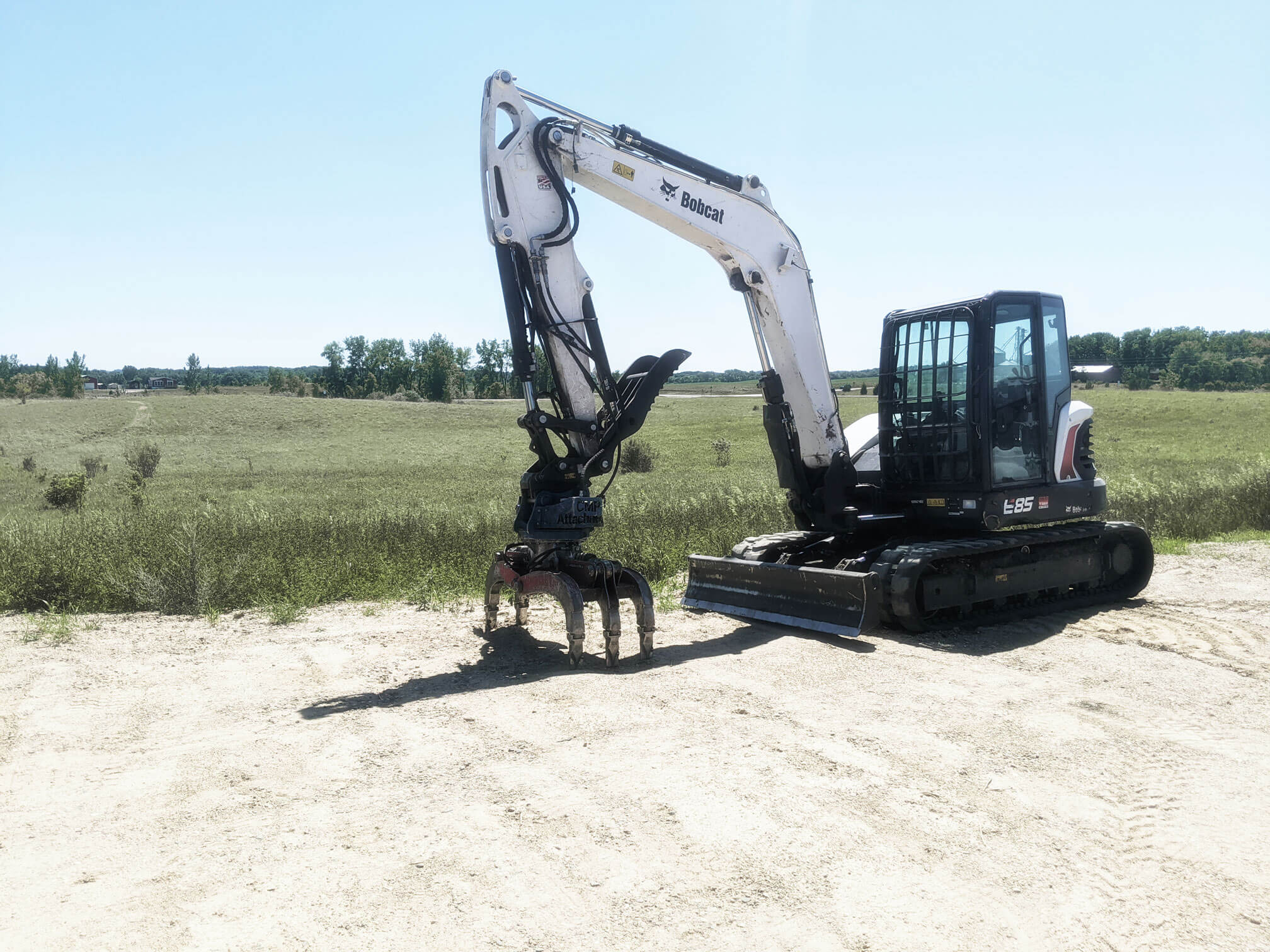 Excavator parked in empty lot. TreeStory has all of the commercial equipment to service any industry & tree removal needs