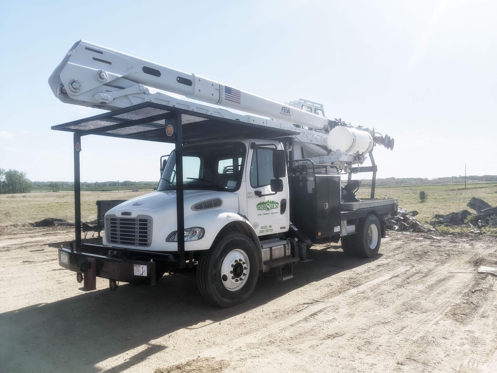Terra Tech Treemaster truck in white sitting on an empty gravel lot. Commercial heavy-duty machinery for tree maintenance