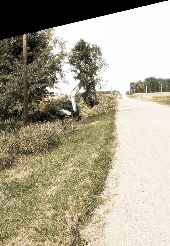 Excavator working alongside gravel road in trees & other vegetation to move & sort brush for TreeStory