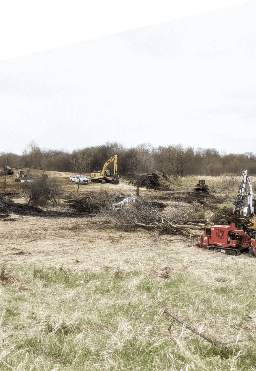 View of TreeStory heavy machinery at work on commercial tree service, including excavator, wood chipper & skidsteer
