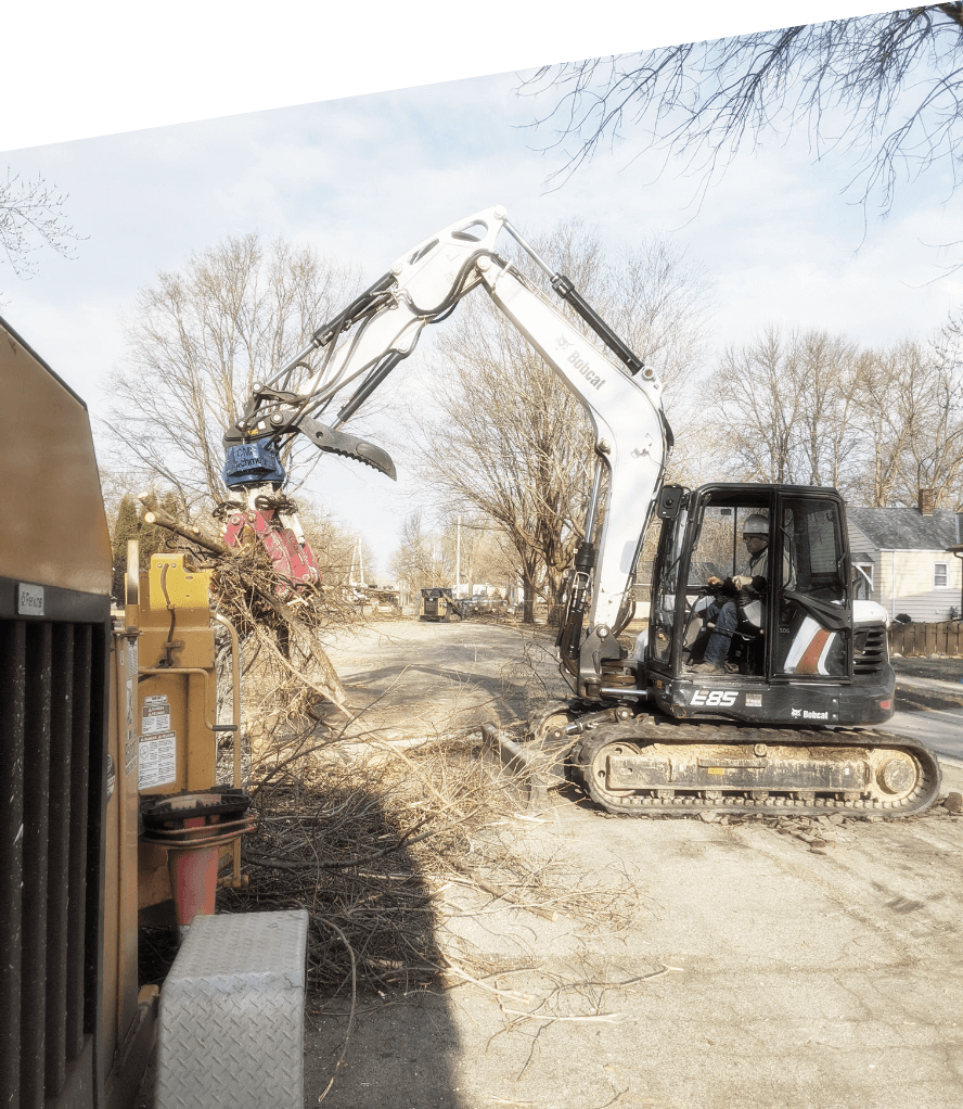 White excavator on residential jobsite putting debris and tree limbs into Treestory woodchipper for site cleanup