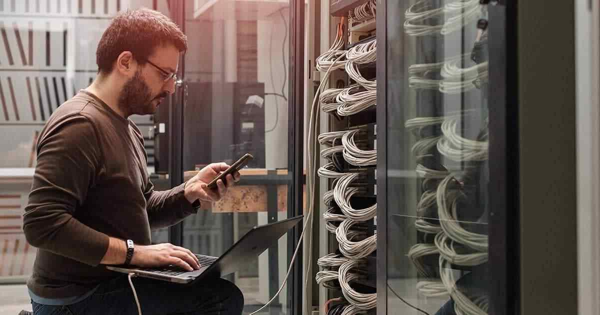 tecnicos trabalhando com celular e servidores
