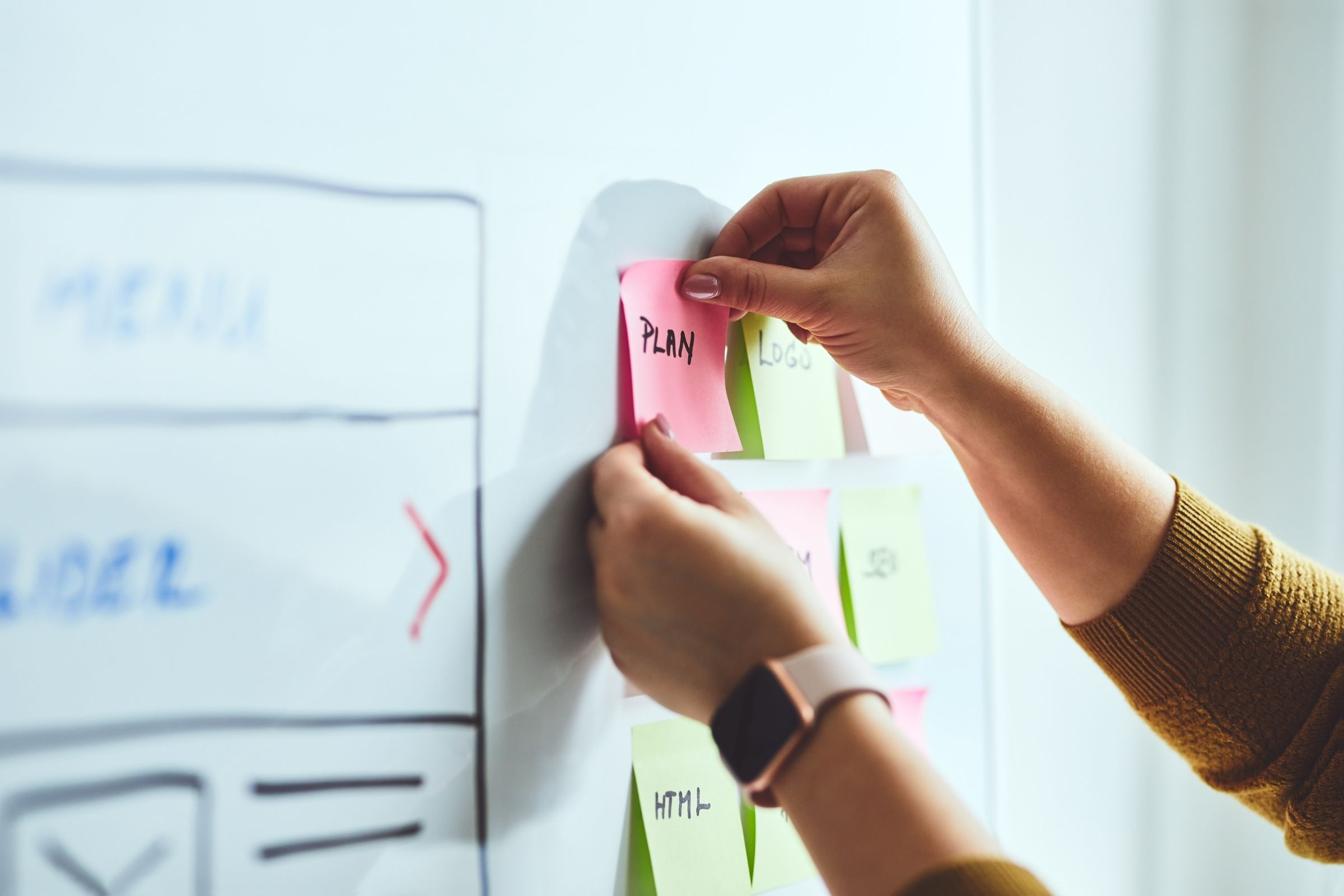 Woman using sticky notes to plan website.
