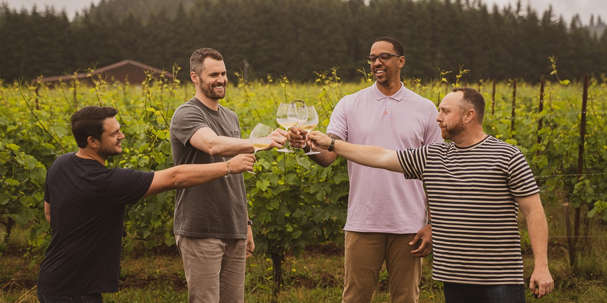 From left: Chase Renton, Kevin Love, Channing Frye, and Jacob Gray toast glasses of wine in front of a vineyard.