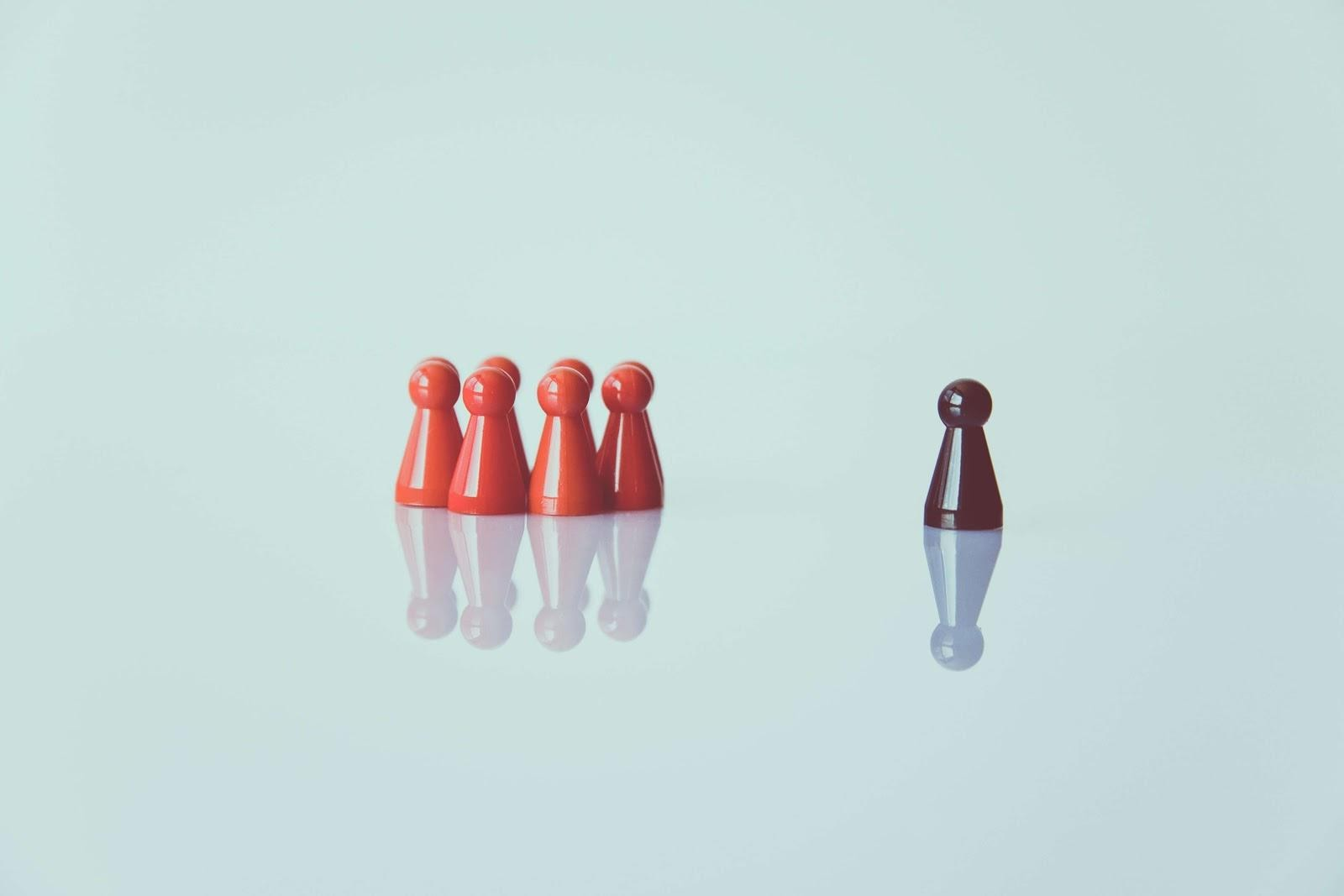 Game pieces displaying laissez faire leadership with one piece set apart