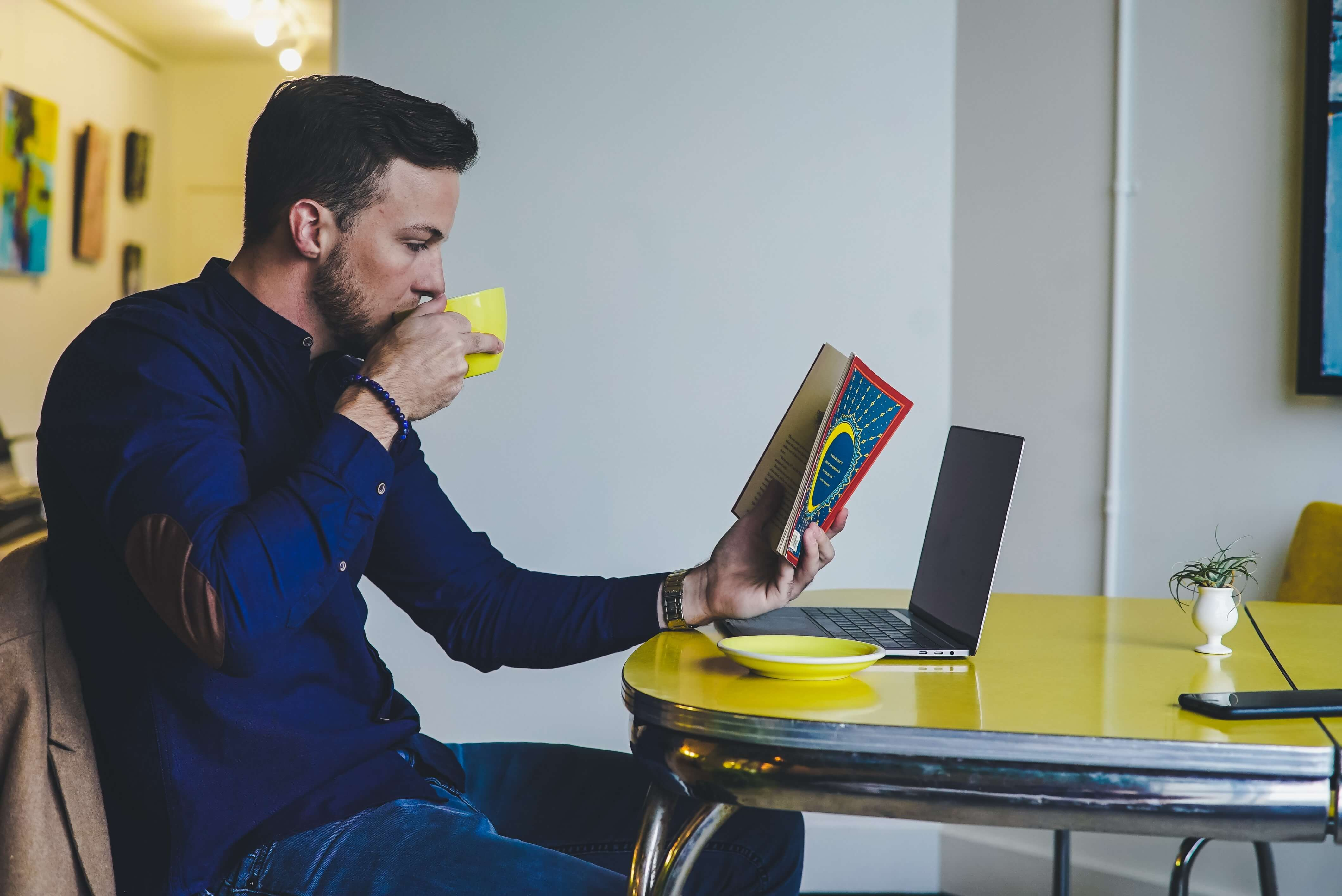 Man drinks coffee at a table while reading about heutagogy and self-managed learning