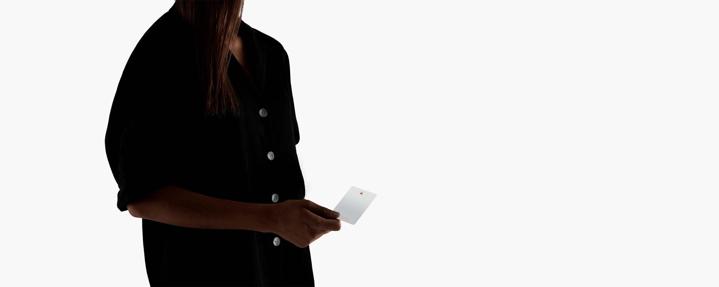 Image of a woman shown from the shoulder down holding a white coppr smart card. She is being illuminated mostly by the infinite white background behind her.