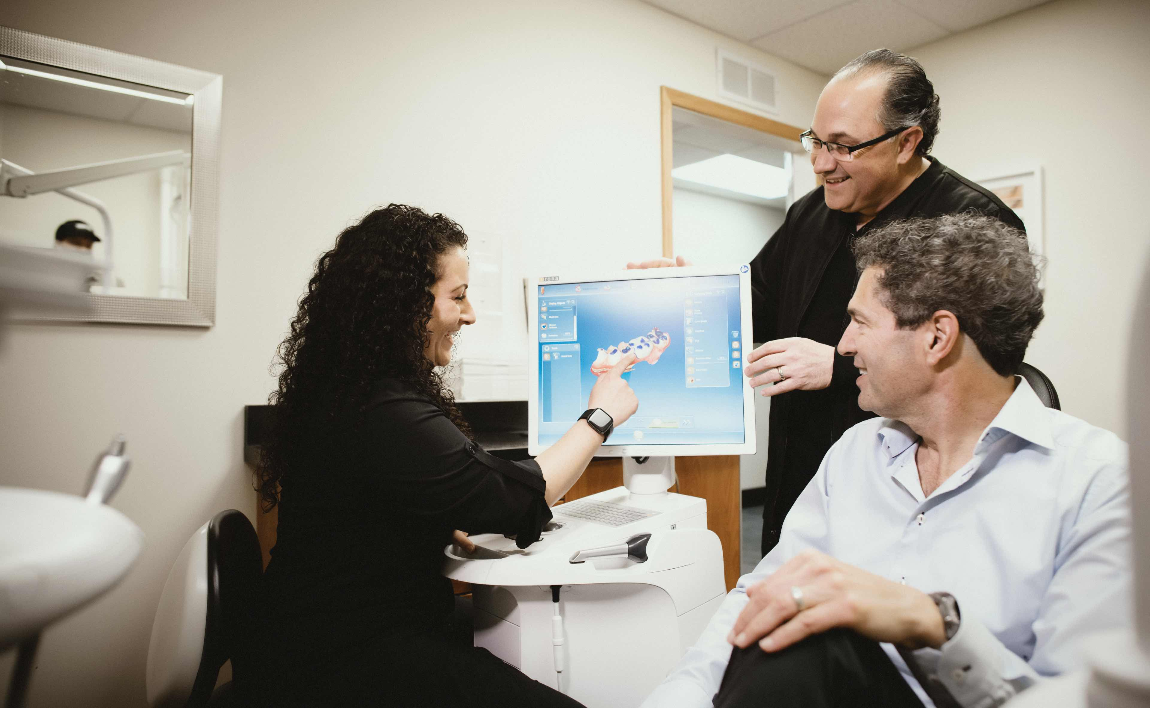 Photo of a team member showing a 3-D model scan to a patient