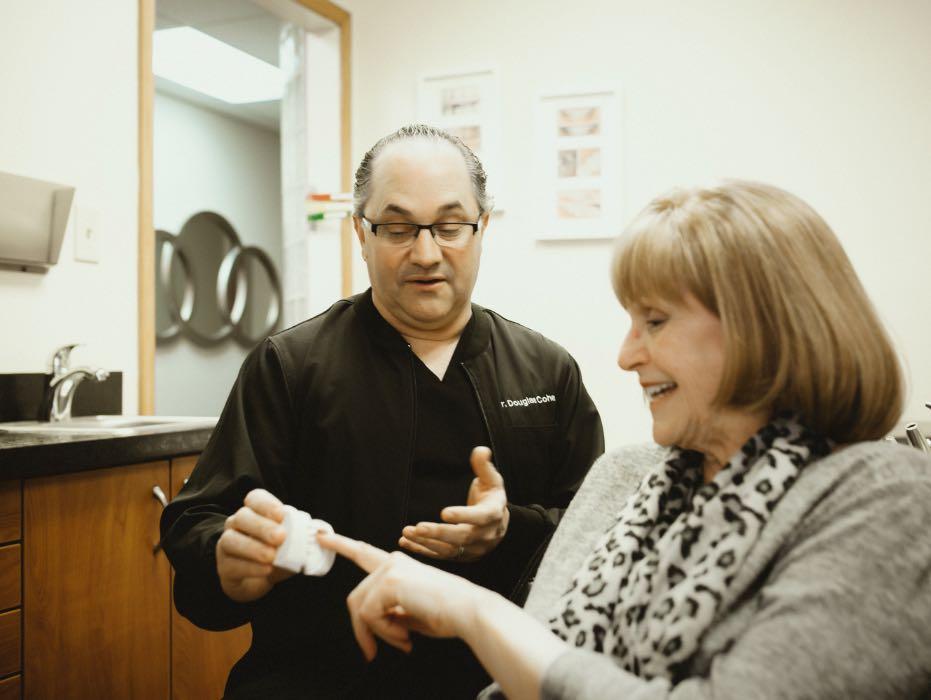 Photo of restorative dentist, Dr. Douglas Cohen showing a dental model to a patient