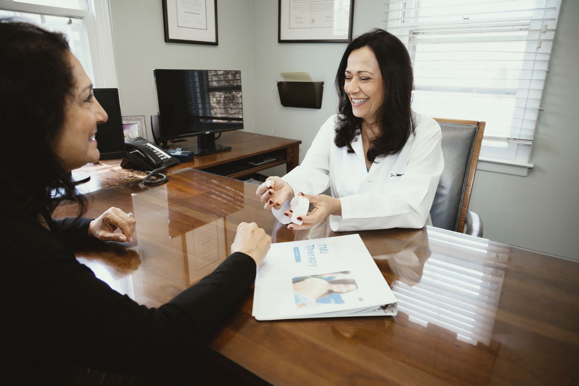 Photo of Dr. Sweeney-Fonesca showing a dental model to a patient