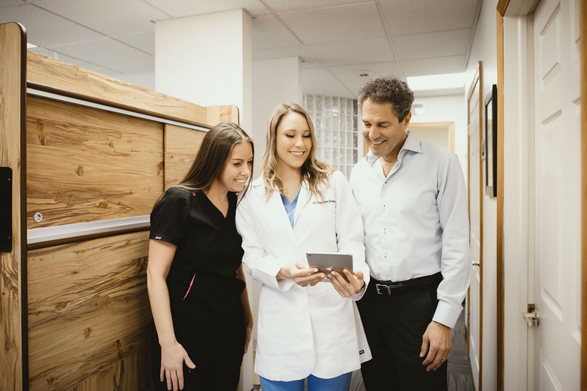 Photo of a dentist, team member, and patient looking at a tablet