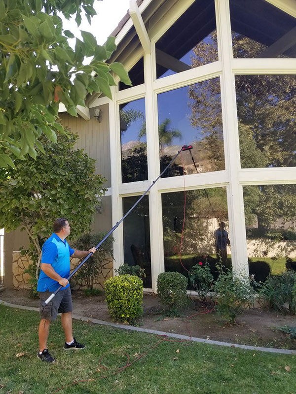 A windows cleaner technician cleaning with pure water system.