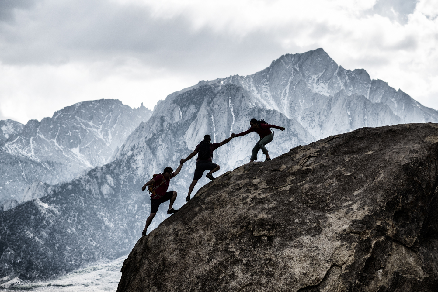 Three people working together to climb a mountain