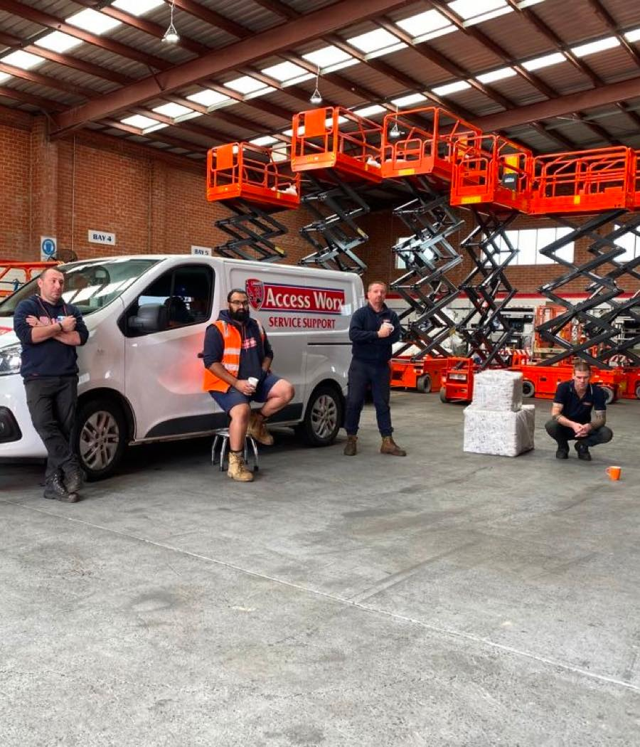 A photo over Access Sales & Spares showing the shop and machine parking lot with raised scissor lifts