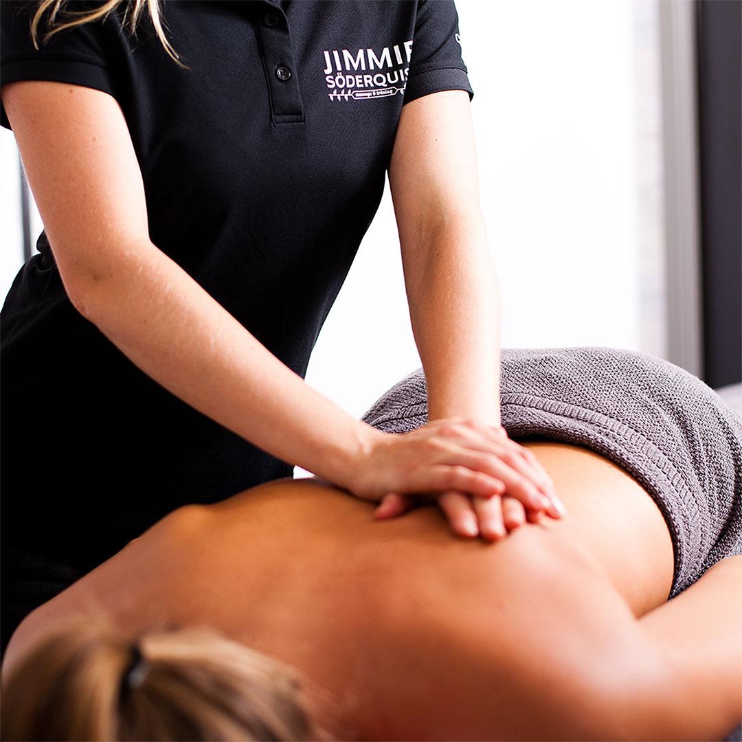 Massör masserar en persons rygg med två händer