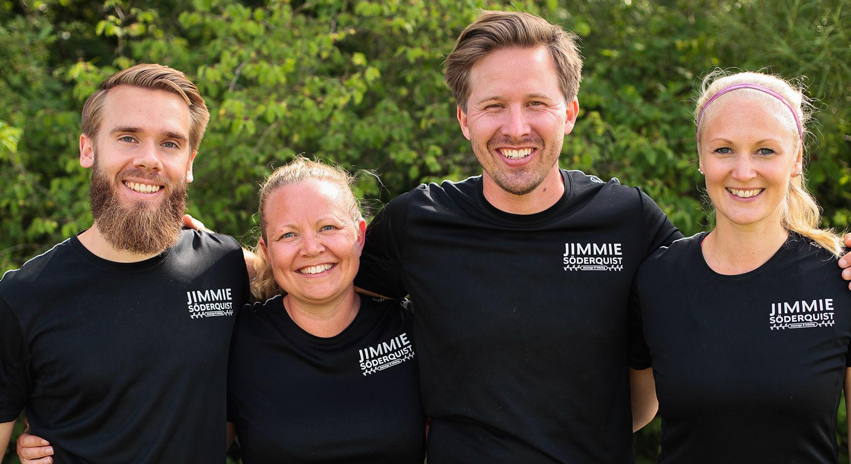 Fyra tränare står på rad och ler mot kameran