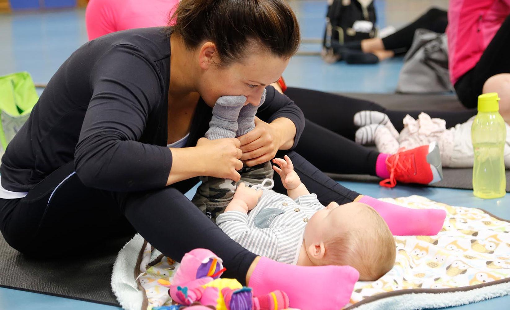 Mamma busar med sin bebis under mamma-träningspass