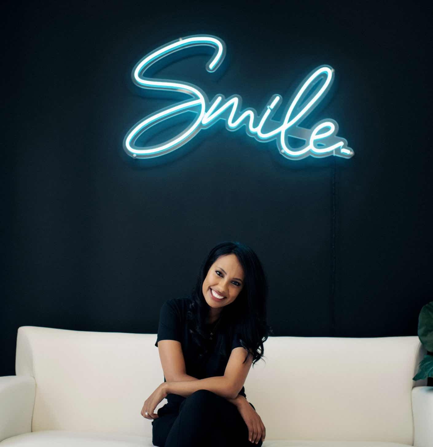 """Photo of Charlotte dentist Dr. Seti Byrd sitting beneath a sign that reads, """"Smile"""""""