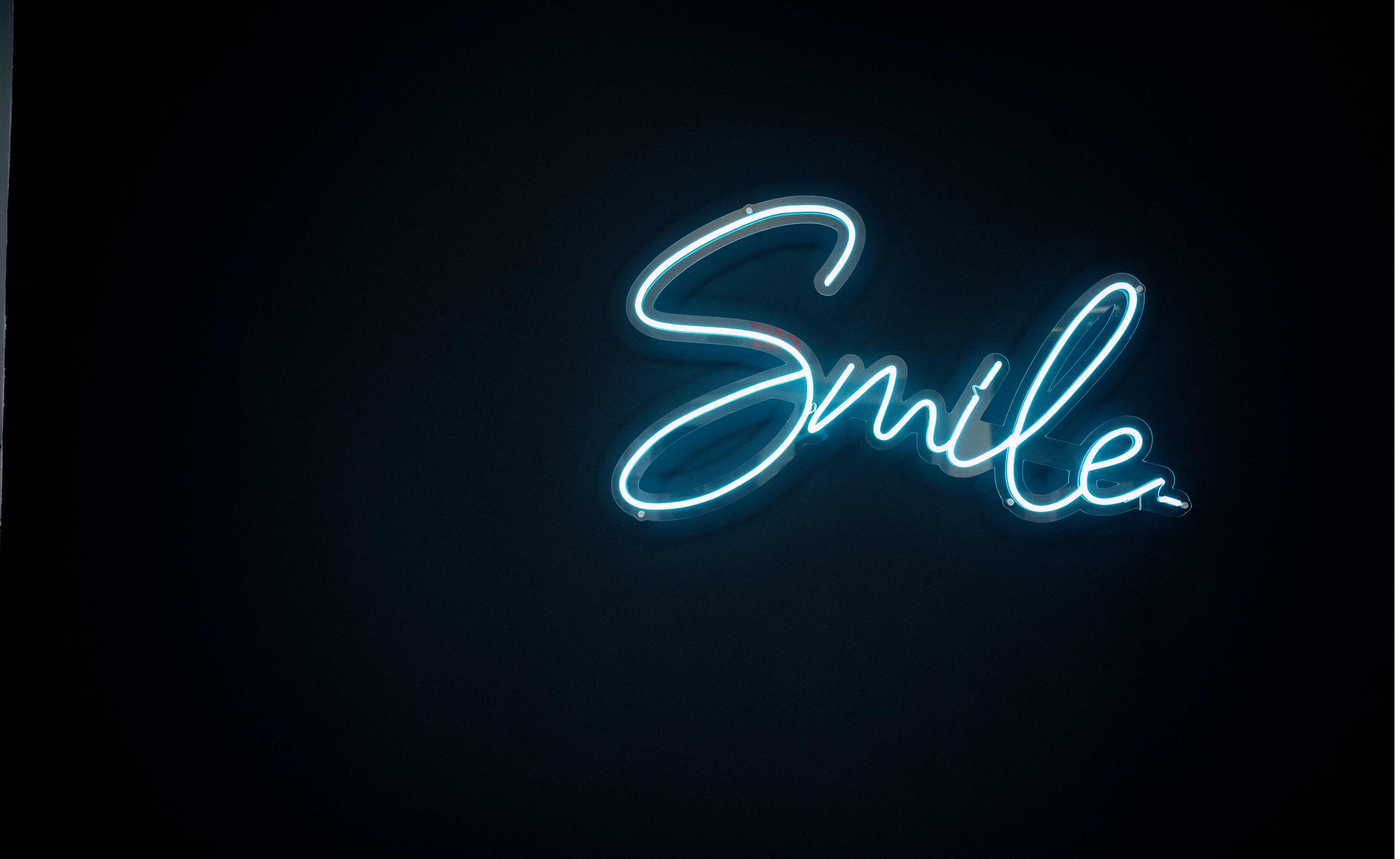 """Photo of a sign on our wall which reads, """"Smile"""" in cursive letters"""