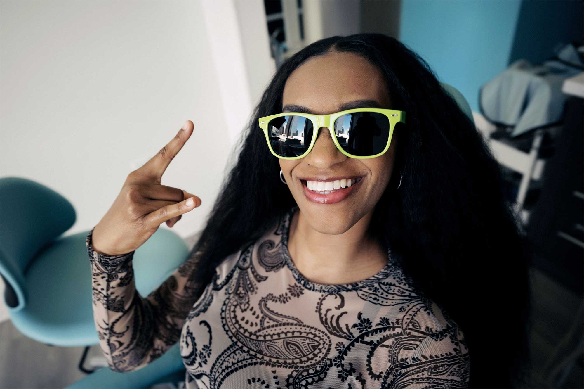Photo of a smiling dental patient wearing yellow sunglasses