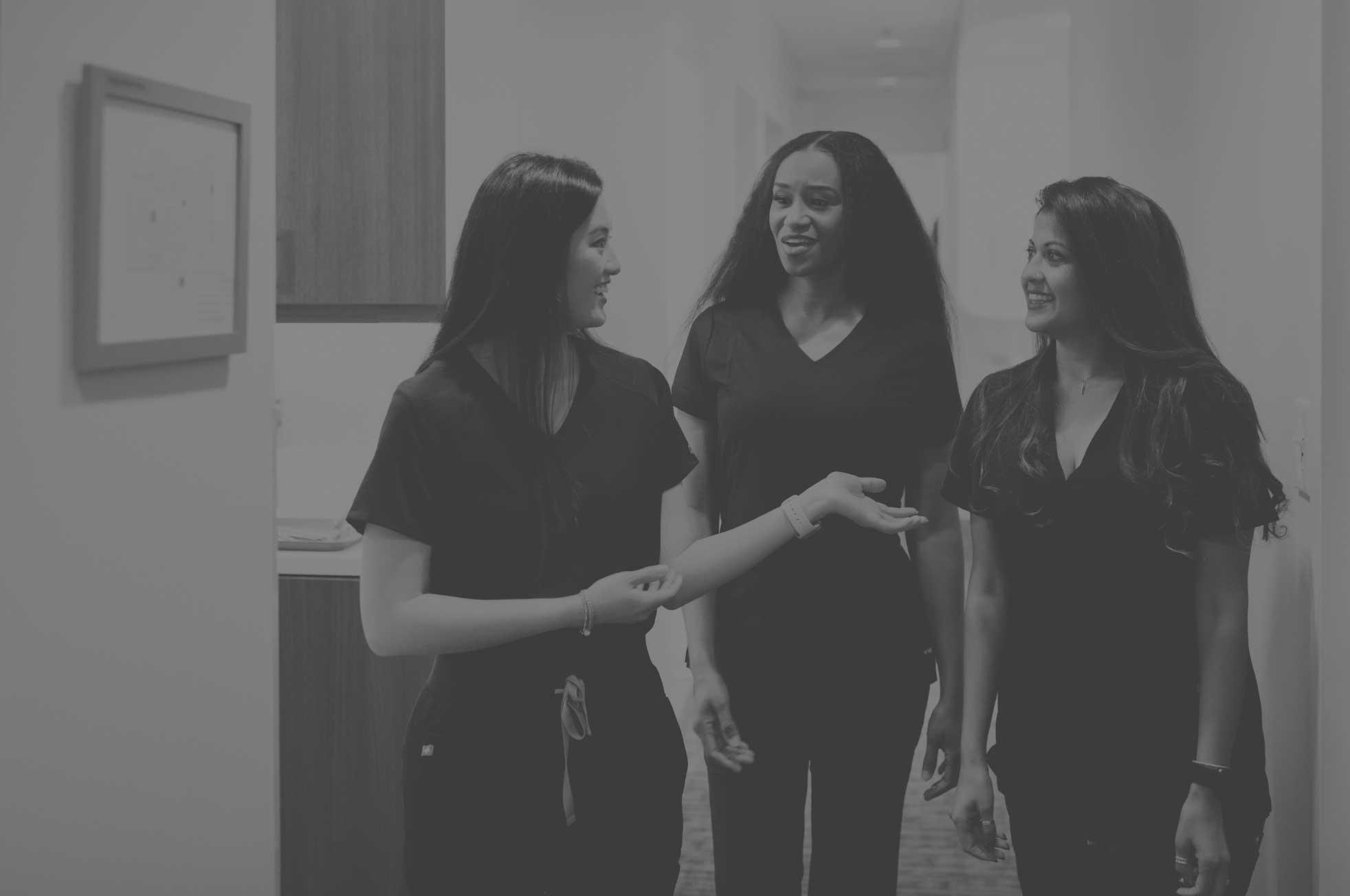 Photo of three dental team members talking in a hallway