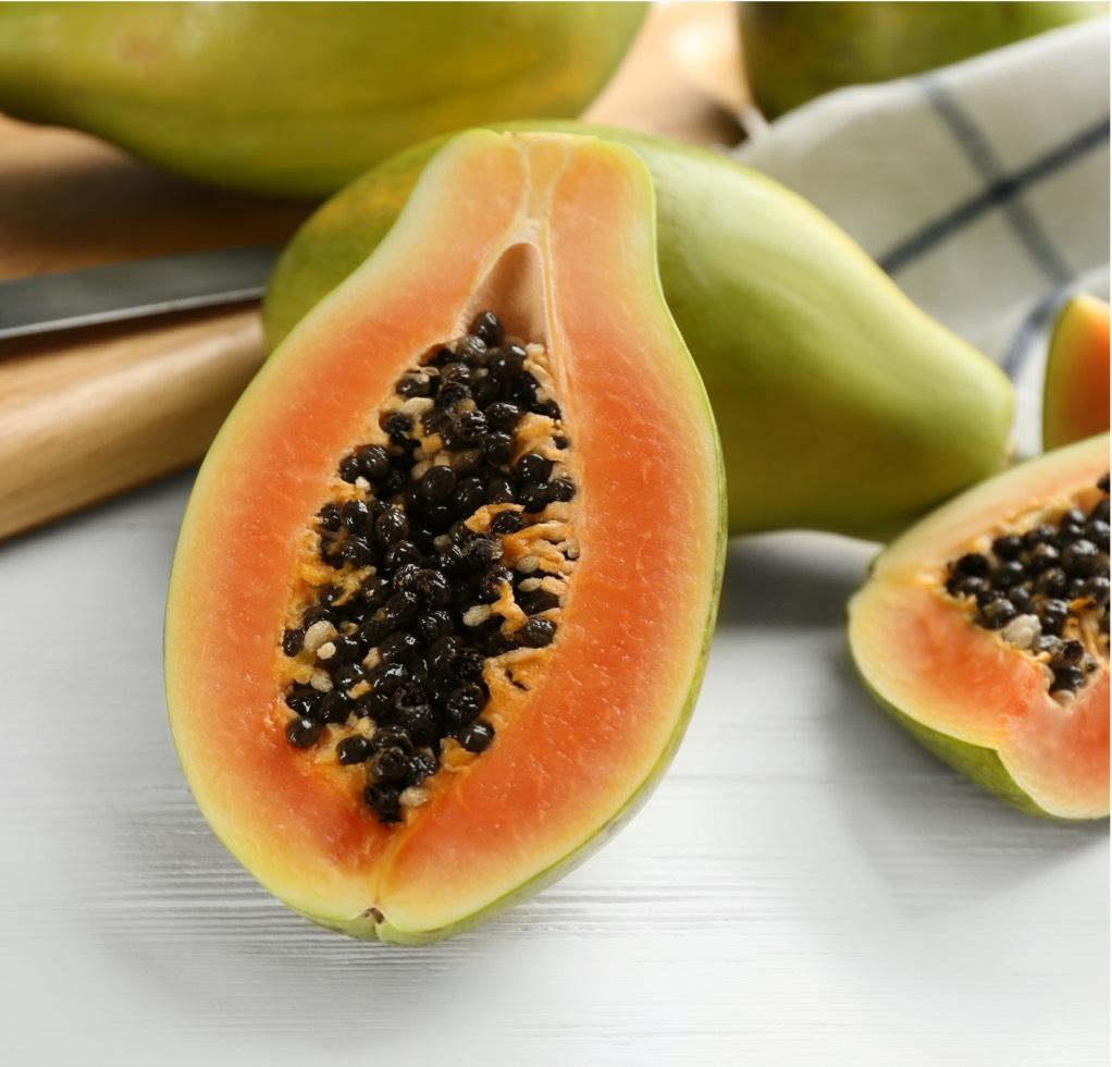 A sliced half of a papaya with its seeds still inside