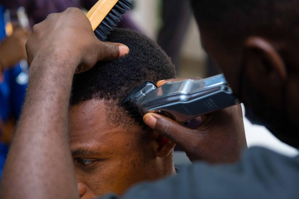 Barber holding clippers and cutting hair