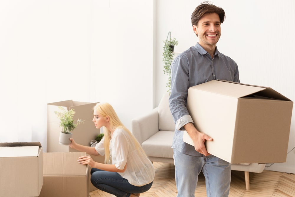Household Move. Happy Couple Packing Stuff In Boxes