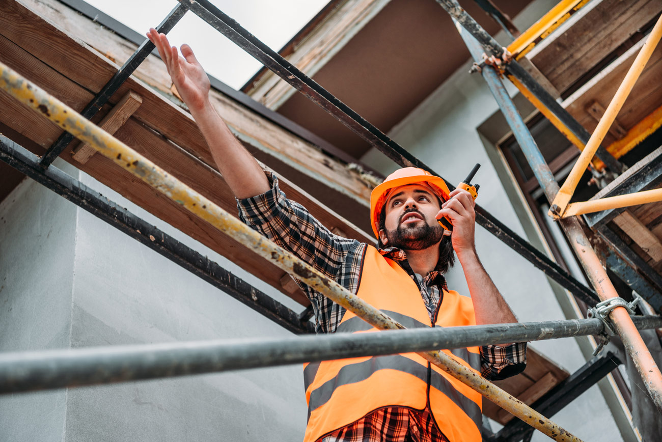 Construction worker pointing forward and talking into radio