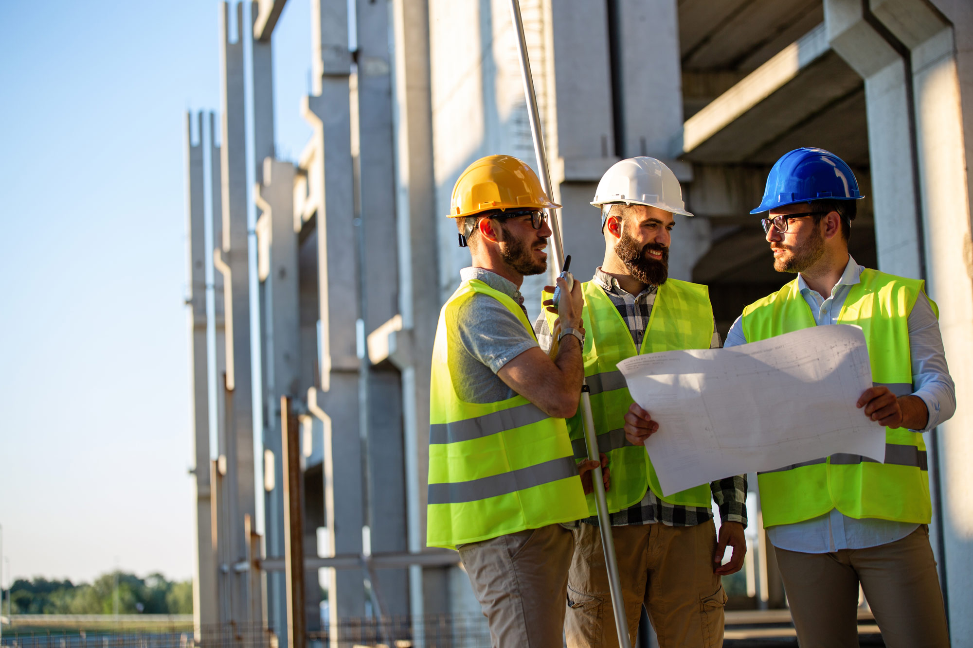 Group of construction worker talking with a radio in hand