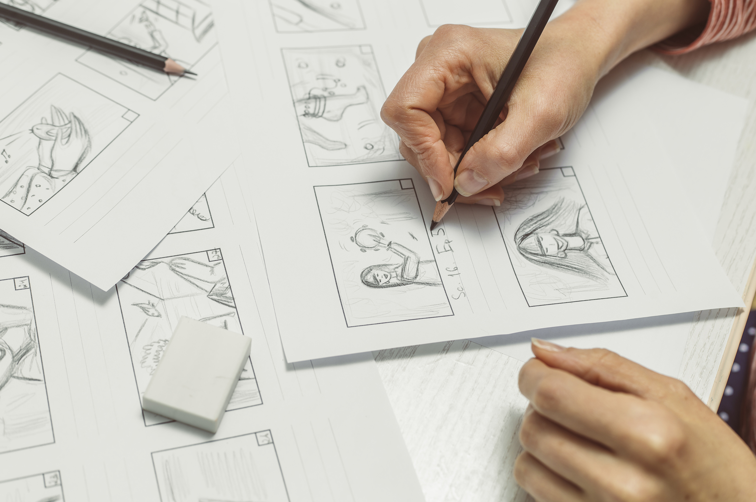 Photo of a hand drawing sketches on paper forming a storyboard.