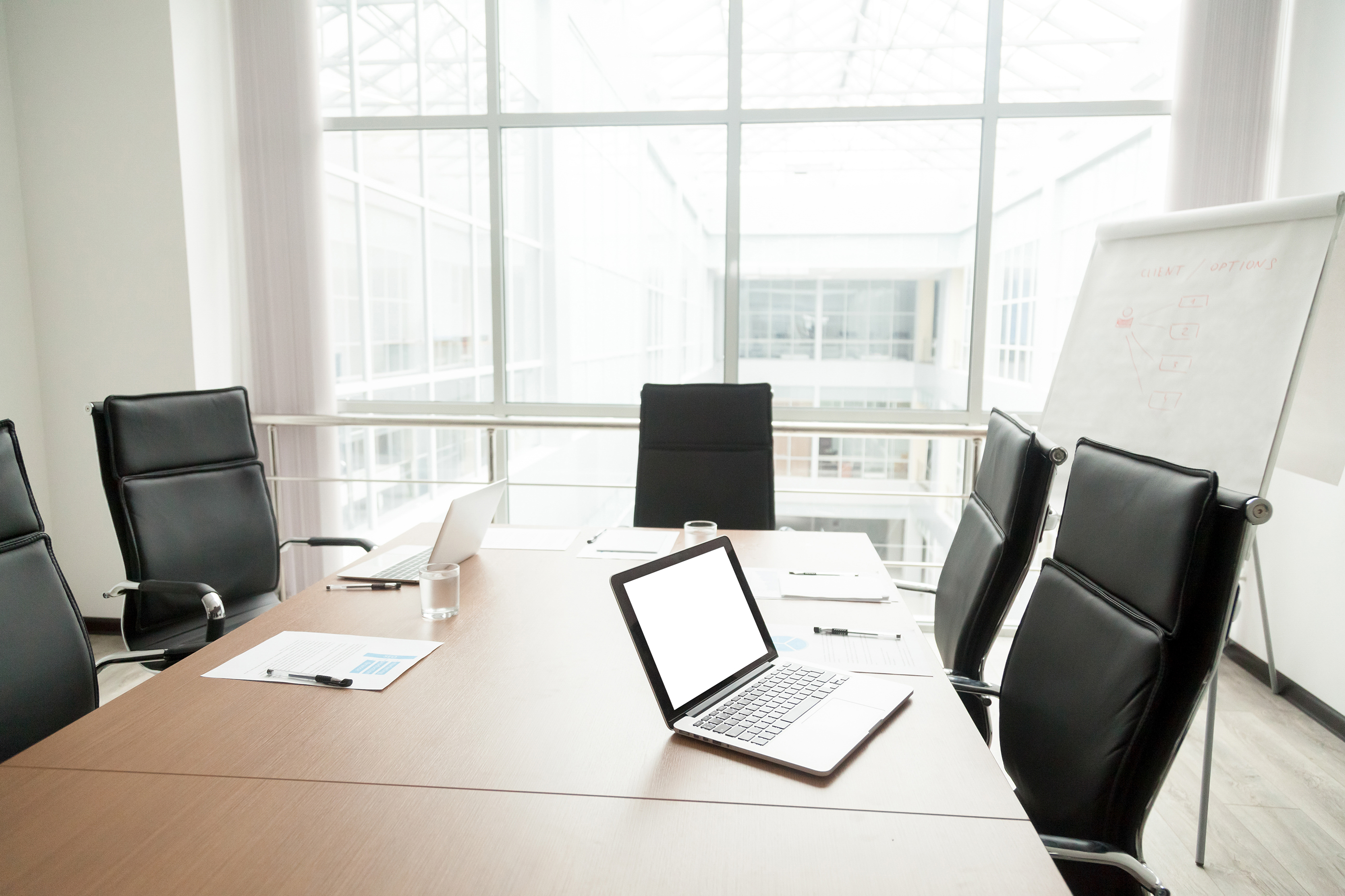 Photo of an empty conference room with an open laptop, blank paper and a presentation-size note board.
