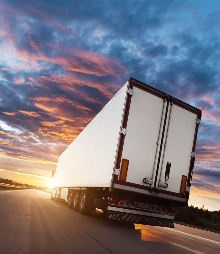 Baksiden av en trailer som kjører på en motorvei i solnedgang.