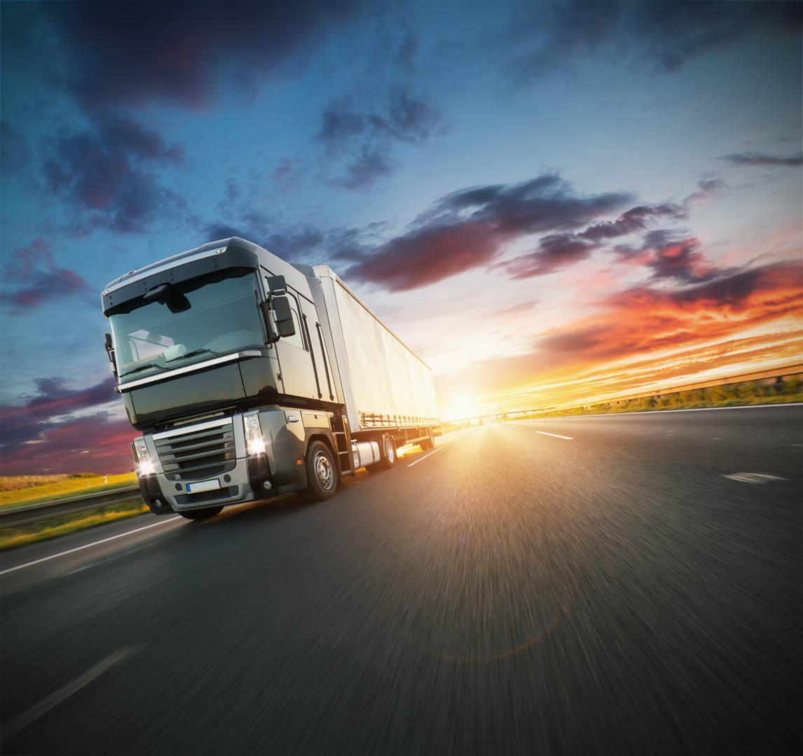 En trailer som kjører på motorveien i solnedgang.