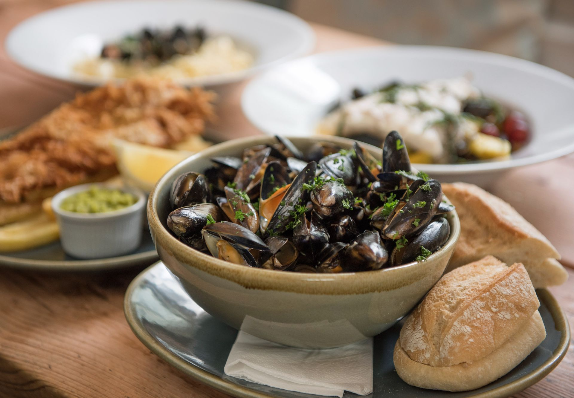 Table-full of freshly prepared food, including mussels and crusty bread