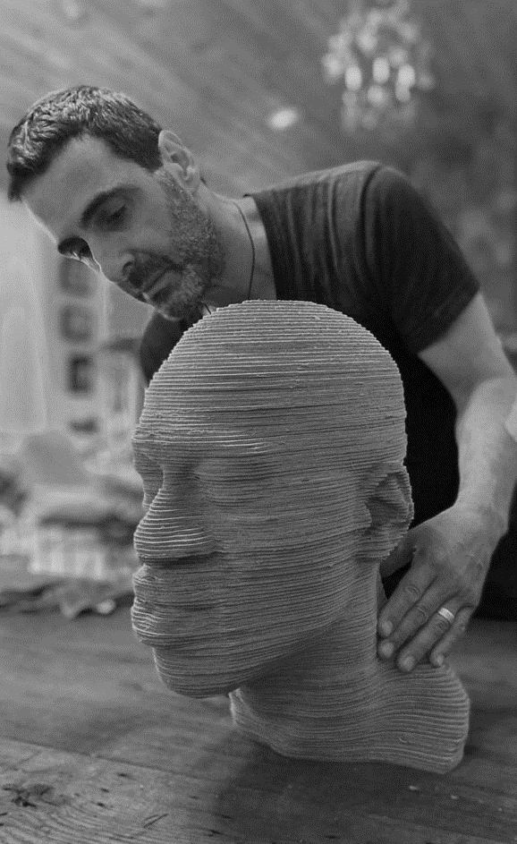 Sculptor working on the layered wood bust of George Floyd in an artist workshop.