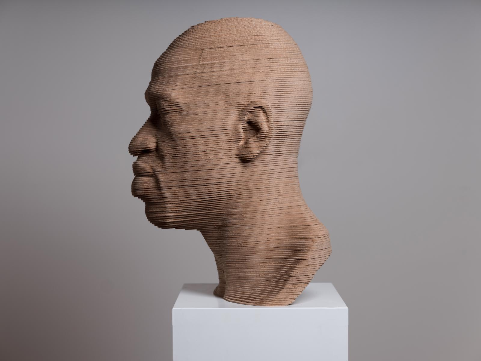 George Floyd Bust Sculpture Looking Left. Made of layered wood on a white marble base.